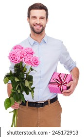 This is for you! Handsome young man holding gift box and stretching out bouquet with pink roses while standing isolated on white background