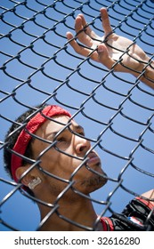 This young basketball player leans up against a chain linked fence at the basketball court.