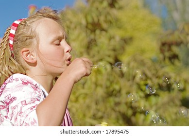 this young girl blows nice floating bubbles