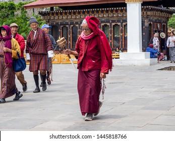 Thiumphu, Bhutan - May 8 2019: elderly woman circling the Memorial Stupa in Thiumphu, Bhutan with a prayer wheel in hand