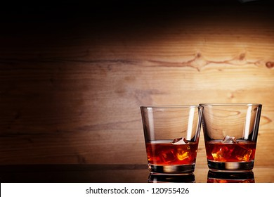tho glasses of whiskey over wooden background
