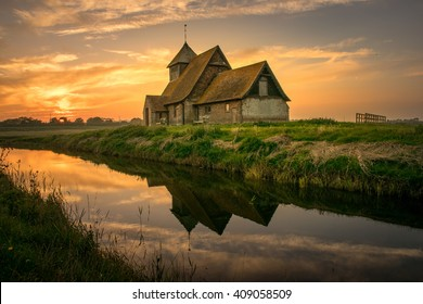 Thomas Becket rural church, Fairfield, Romney marsh, reflected in the river at sunset