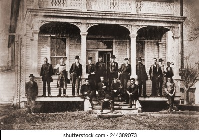 Thomas Edison with the engineers and technicians of his Menlo Mark workshop. Edison is under the central arch, leaning against the support with his hands in his pockets. Ca. 1880.