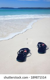 Thongs with Australian flag  on the beach with footprints leading into the ocean.  Holiday, vacation, travel, leisure, unwind