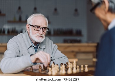 thooughtful senior man playing chess in cafe and looking at opponent