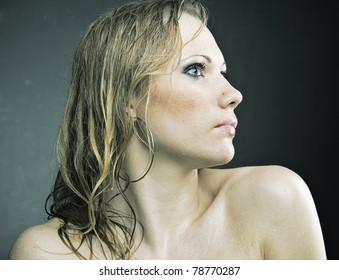 Thoracic portrait of pretty wet and nude girl staying forward to camera, looking away