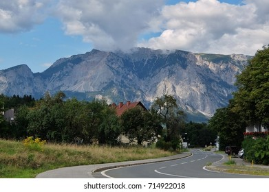 Thorl, Austria - August, 20th, 2017. View of road curves in small town near the Austrian-Italian border with mountains and cloudy sky in background.