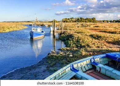 Thornham, Norfolk, England, United Kingdom - October 12, 2012: Fishing boats moored on coastal river in marshland on North Norfolk coast, East Anglia, England, United Kingdom