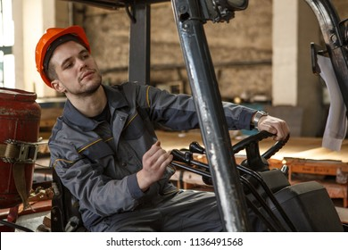 Thorougful worker of metal stock in orange hardhat and protective suit in process of driving forklift. Concentrated toung man looking carefully while transferring material.