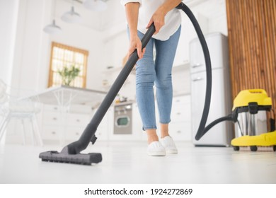 Thorough cleaning. Slender woman in jeans and moccasins doing afternoon vacuuming in white kitchen, no face