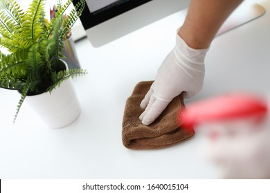 Thorough cleaning workplace, near home computer. Human hand in white silicone glove wipes surface table with towel. Apartment and office cleaning, cleanliness service. Maid is cleaning hotel room.