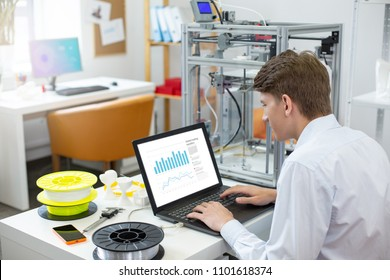 Thorough preparation. Charming young man sitting at his workplace in the office and creating a presentation on laptop, preparing to give a speech