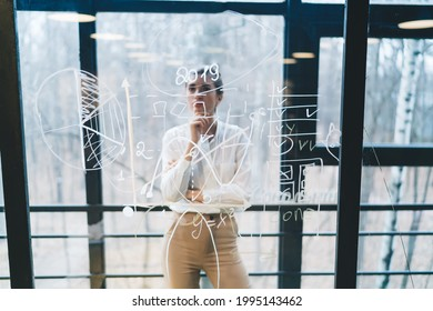 Though glass view of smart female in office clothes looking at data on transparent board while working and making decision