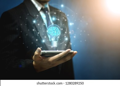 Thought technology,The light bulb on the smartphone in the hands of a businessman with a drawing of the brain inside the lamp - a picture
