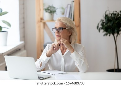 Thoughtful 60 years old businesswoman using laptop, pondering online project or startup ideas. Employee thinking about business vision sitting at office desk, manager solving business problem.