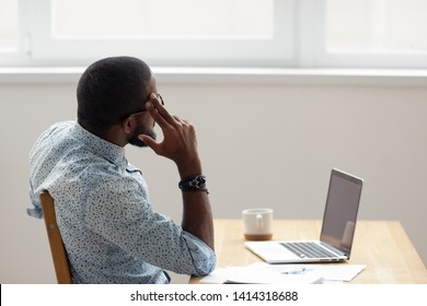 Thoughtful African American businessman looking out window sitting at office desk. Relaxed worker finished work completed task taking break after hard workday putting head on hand. Side view