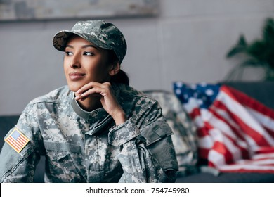 thoughtful african american female soldier in military uniform with american flag on background