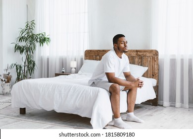 Thoughtful African American Man Thinking Sitting On Bed In Bedroom At Home In The Morning. Thoughts About Life, Stressful Modern Life Concept. Free Space For Text