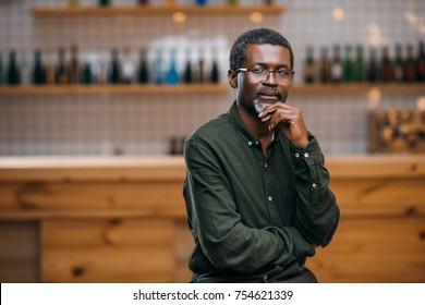 thoughtful african american mature man in front of bar counter