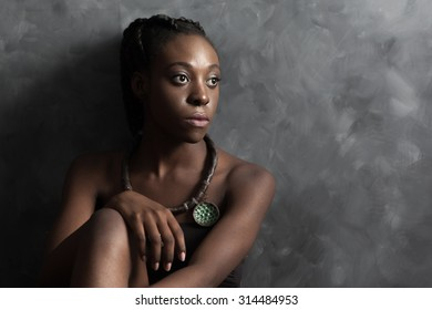 the thoughtful African woman with brilliant black skin with a ceramic ethnic necklace of handwork sits and embraces the hands knees. Studio conceptual photo against a dark background