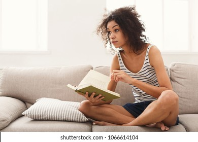Thoughtful african-american student girl reading book. Young woman studying at home, sitting on beige couch, copy space