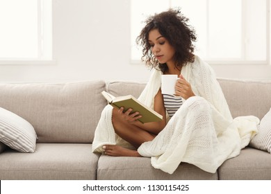 Thoughtful african-american student girl reading book. Young woman studying at home, sitting on beige couch wrapped up in white blanket and holding coffee cup, copy space