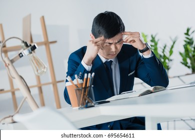 thoughtful asian businessman at workplace