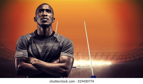 Thoughtful athlete standing with arms crossed against rugby stadium