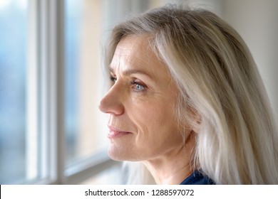Thoughtful attractive mature blond woman with blue eyes looking out of a window with a quiet smile in a close up profile portrait