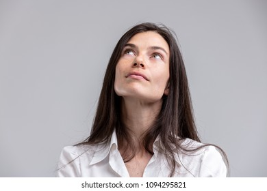 Thoughtful attractive woman looking up into the air with a calm contemplative expression isolated on grey