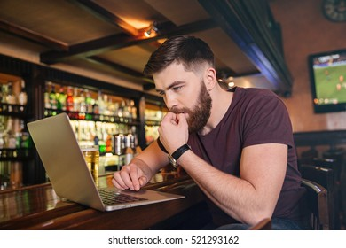 Thoughtful attractive young man sitting and using laptop in bar