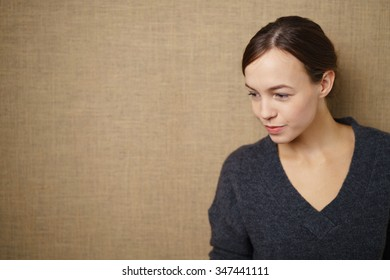Thoughtful Attractive Young Woman Looking Down Against Seamless Brown Wall with Copy Space on the Left.