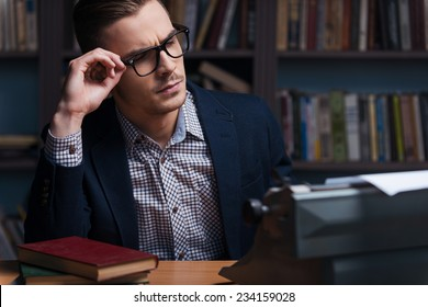Thoughtful author. Thoughtful young author working at the typewriter and adjusting his eyeglasses while sitting at his working place with bookshelf in the background