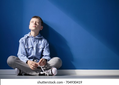 Thoughtful autistic boy sits with crossed legs on white floor against blue wall