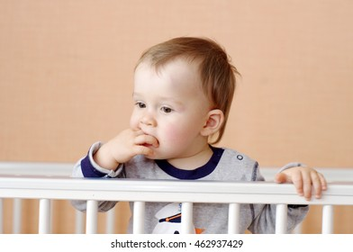 thoughtful baby age of 1 year in white bed