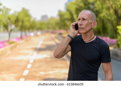 Thoughtful bald senior tourist man talking on mobile phone on the side of the street at peaceful park in Bangkok Thailand