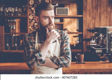 Thoughtful barista. Young bearded man in apron looking away and keeping hand on chin while standing at bar counter