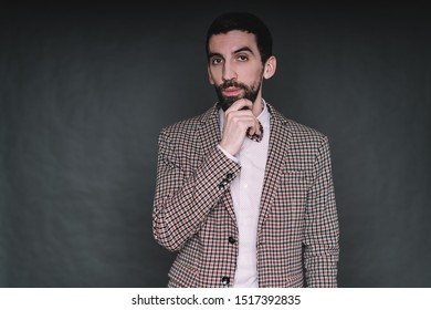 Thoughtful bearded male hipster in old-fashioned unbuttoned checkered suit with bow tie thinking while stroking beard and looking at camera