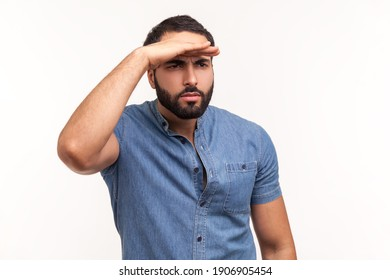 Thoughtful bearded man looking far away at distance with hand over head, attentively searching for bright future. Indoor studio shot isolated on white background