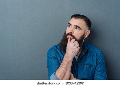 Thoughtful bearded man looking up into the air with his thumb to his mouth over a grey studio background with copy space