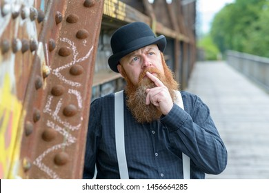 Thoughtful bearded man in a retro style bowler hat and braces standing leaning against an old bridge with a finger to his lips looking up with a contemplative expression