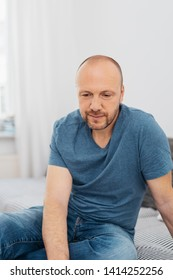 Thoughtful bearded middle-aged man at home relaxing on a sofa or day bed staring down at the floor with a quiet smile and pensive expression