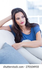 Thoughtful beautiful brunette sitting on the couch in the living room