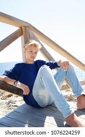 Thoughtful beautiful nordic blond teenager sitting on wooden stairs on summer beach coastal destination on sunny holiday, nature outdoors. Healthy male relaxing, travel recreation leisure lifestyle.