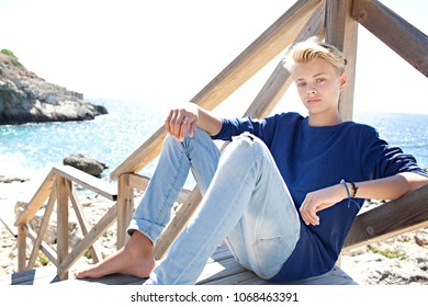 Thoughtful beautiful nordic teenager sitting on wooden stairs, summer beach coastal destination on sunny holiday, nature outdoors. Healthy male relaxing, travel recreation leisure lifestyle, looking.