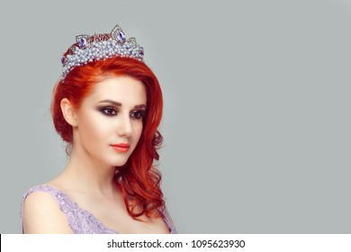 Thoughtful beautiful redhead girl in a purplish pearls crown isolated light gray green color background wall looking to the side slight smile on face smiling pretty woman with crystal crown on head