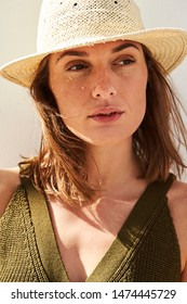 Thoughtful and beautiful woman looking away in sunhat