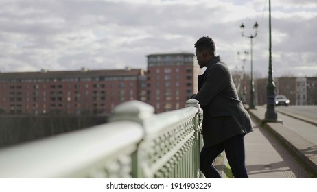 Thoughtful black African man thinking about life on top of a bridge