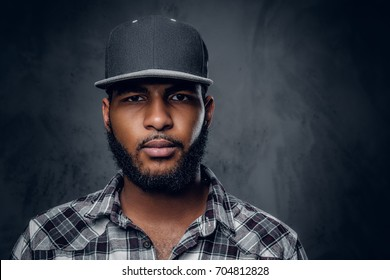 Thoughtful Black, bearded hipster male dressed in a fleece shirt and baseball cap.