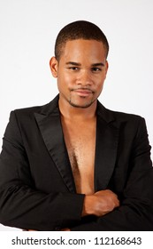 Thoughtful black man with no shirt on, in a black tux jacket